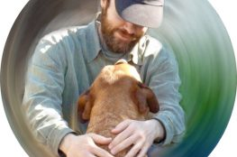 Man wearing hat, giving dog a cuddle, blurred background.