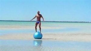 Man balancing on exercise ball.