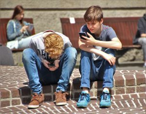 Children outside, all looking at smartphone screens.
