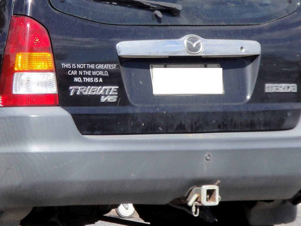 """Photo of funny sticker on car, text reads: """"This is not the greatest car in the world, no this is a Tribute V6 Mazda""""."""