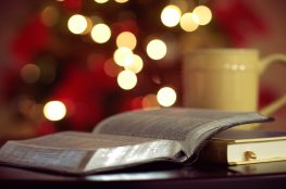 Apparent Christmas scene, Bible on table, bokeh effect.