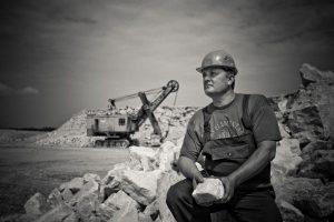 Strong man holding broken rock.