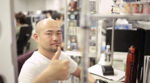 Man sitting (Hideki Kamiya), giving thumbs up.