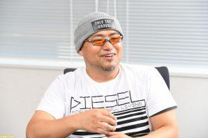 Hideki Kamiya smiling, sitting in an office, apparently talking with someone.