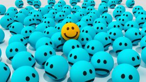 A crowd of blue 3D smiley faces with frowns, a single yellow smiley face with a smile, raised above/standing out from the unhappy crowd.