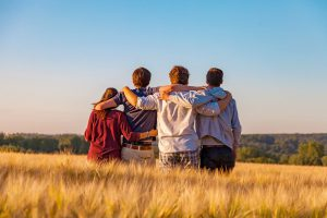 Young friends, arms around each other's shoulders, standing in field.