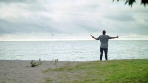 Man with Bible in hand and his arms raised, on the beach and looking towards the sky.