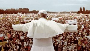 Photo of Pope John Paul II standing in front of a large crowd, in Poland.