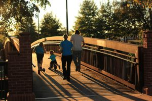 Photo of parents with children walking over a bridge.