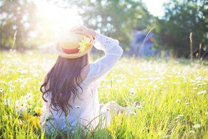 Photo of pretty woman sitting in a beautiful field, sun shining brightly.