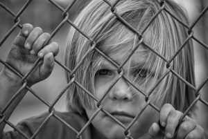 Photo of young and sad disadvantaged-looking boy behind a wire fence.